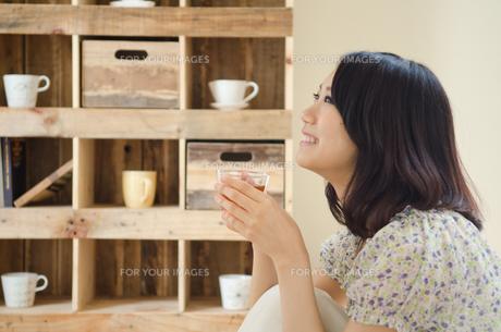 お茶の入ったグラスを持って笑う女性の素材 [FYI01077336]
