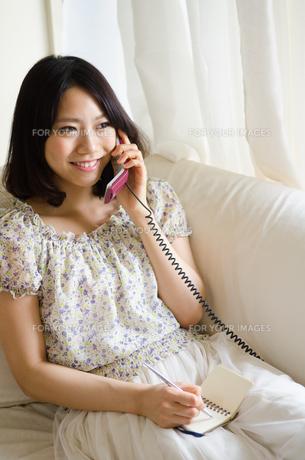 部屋の中で電話をしている女性の素材 [FYI01077338]