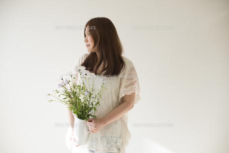 ポットに入った白いデイジーを持つ女性の素材 [FYI01077343]