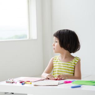 折り紙で遊びながら外を眺める女の子の素材 [FYI01077358]