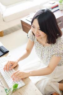 床に座ってパソコンを操作している女性の素材 [FYI01077360]