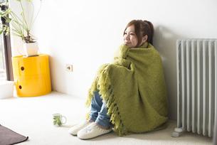 緑の毛布にくるまって座る女性の素材 [FYI01077366]