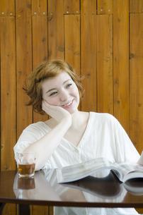 机に頬杖を付いて微笑むハーフの女性の素材 [FYI01077369]