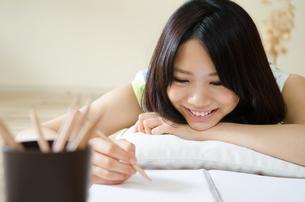ノートに何かを書きながら笑う女性の素材 [FYI01077370]