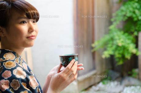 お茶の入った湯のみを持つ着物姿の女性の素材 [FYI01077372]