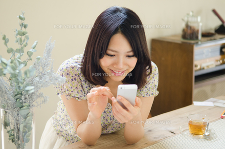 部屋の中でスマートフォンを操作する女性の素材 [FYI01077376]