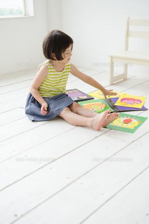 床に座って絵本を触る女の子の素材 [FYI01077380]