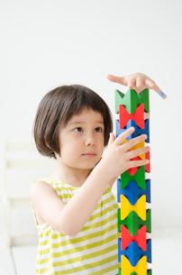 知育おもちゃで真剣に遊ぶ女の子の素材 [FYI01077381]