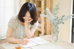テーブルでノートにメモをしている女性の素材 [FYI01077382]