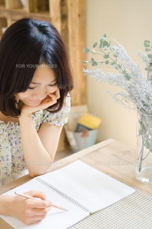 テーブルでノートにメモをしている女性の素材 [FYI01077390]