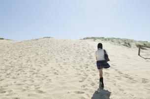 ビーチを歩く制服姿の女の子の後ろ姿の素材 [FYI01077391]