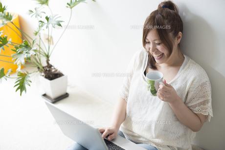 カップを片手にノートパソコンを操作する女性の素材 [FYI01077395]