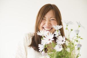 白いデイジーを持って笑う女性の素材 [FYI01077398]