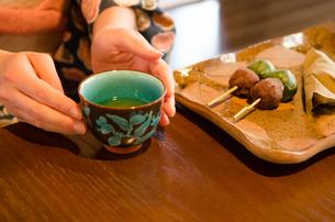 机にある和菓子と湯のみに添えられた着物姿の女性の手の素材 [FYI01077407]