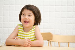 イスに座って笑う女の子の素材 [FYI01077413]