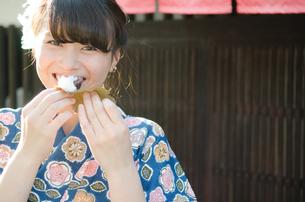 柏餅を食べながら笑う着物姿の女性の素材 [FYI01077417]