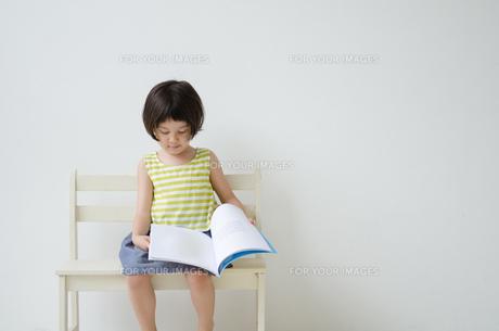 ベンチに座って絵本をめくる女の子の素材 [FYI01077424]