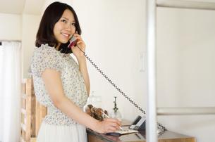 部屋の中で電話をしている女性の素材 [FYI01077426]