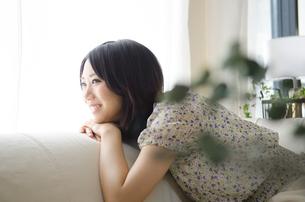 ソファに座って笑う女性の素材 [FYI01077427]