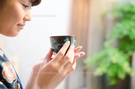 お茶の入った湯のみを持つ着物姿の女性の素材 [FYI01077429]