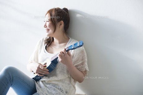 ウクレレを持って笑う女性の素材 [FYI01077439]