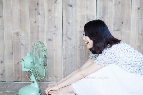 扇風機に向かって声を出している女性の素材 [FYI01077441]
