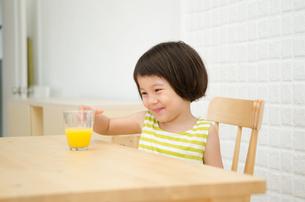 テーブルのオレンジジュースを見て笑う女の子の素材 [FYI01077445]