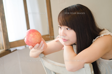 りんごを眺めている女性の素材 [FYI01077448]