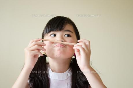 鉛筆を持っておどけた顔をする女の子の素材 [FYI01077451]