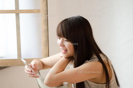 イスに座ってスマートフォンを操作する女性の素材 [FYI01077452]