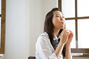 笑顔でパンを食べる制服姿の女性の素材 [FYI01077458]