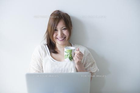 カップを片手にノートパソコンを操作する女性の素材 [FYI01077459]