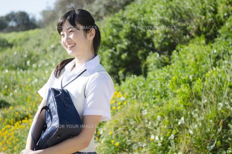 カバンを抱えて微笑む制服姿の女の子の素材 [FYI01077461]