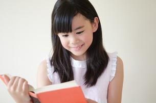 本を読みながら笑っている女の子の素材 [FYI01077464]