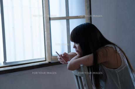 イスに座ってスマートフォンを操作する女性の素材 [FYI01077465]