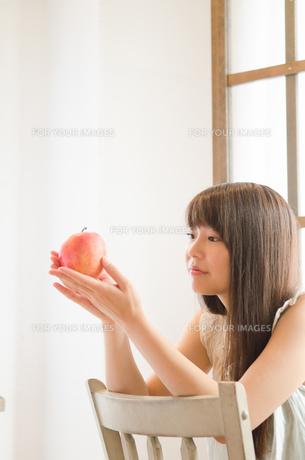 イスに座ってりんごを眺める女性の素材 [FYI01077466]