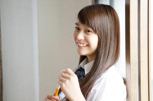 ペンを持って笑っている制服姿の女性の素材 [FYI01077478]