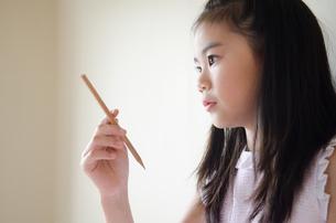 鉛筆を持って考えている女の子の素材 [FYI01077480]