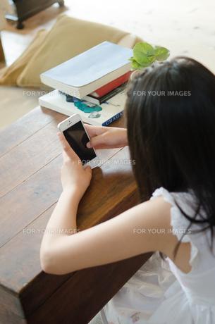 リビングでスマートフォンを操作する女の子の素材 [FYI01077496]