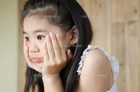 頬杖を付いて考えている女の子の素材 [FYI01077497]