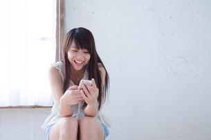 イスに座って携帯電話を見ている笑顔の女性の素材 [FYI01077498]