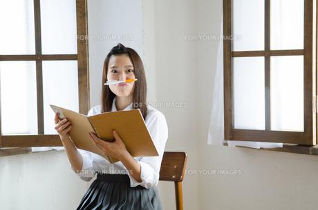 ノートを持ってペンを鼻の下に挟んでいる制服姿の女性の素材 [FYI01077500]