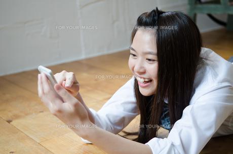 イスに座ってスマートフォンを操作する女性の素材 [FYI01077501]