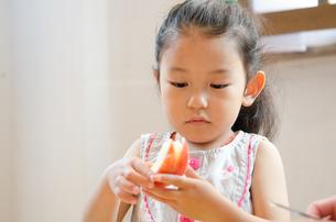 うさぎの形に切ったりんごを持つ女の子の素材 [FYI01077504]