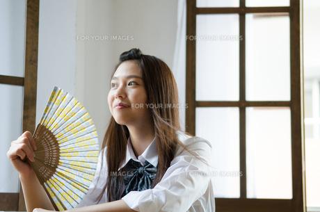 扇子をあおいでいる制服姿の女性の素材 [FYI01077517]