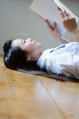 床に寝転がってノートを眺める制服姿の女性の素材 [FYI01077518]