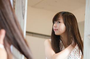 鏡の前で髪をセットする女性の素材 [FYI01077519]
