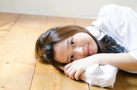 床に寝転んでこちらを見る制服姿の女性の素材 [FYI01077523]