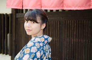 格子の家の前で振り返る着物姿の女性の素材 [FYI01077524]