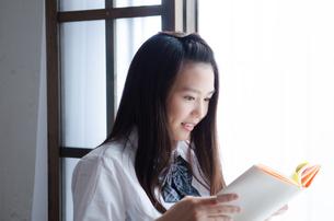 本を読んでいる制服姿の女性の素材 [FYI01077530]